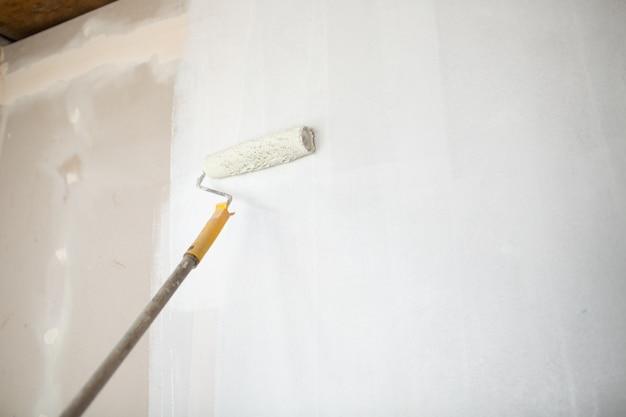 Rodillo de pintura blanca en la mano con pared de yeso