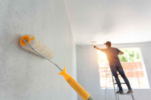Rodillo de pintura interior y el trabajador en el fondo. concepto de remodelación del hogar.