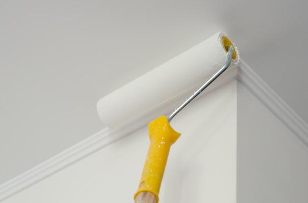 Rodillo de pintura con mango amarillo. proceso de pintura de techos y paredes. blanco copyspace