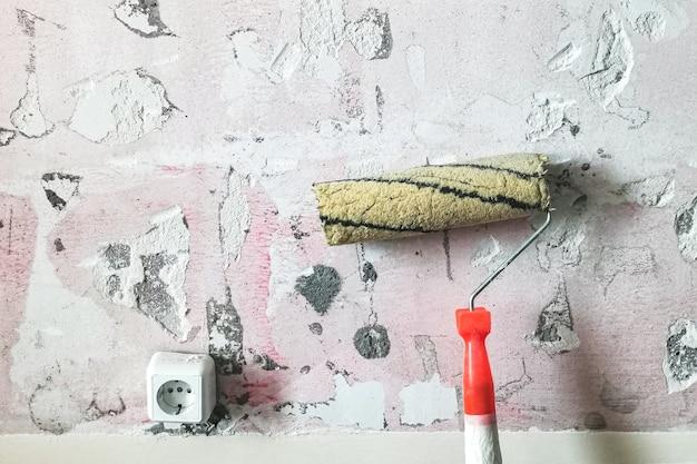 Rodillo de pintura usado sucio con el telón de fondo de una pared ruinosa con azulejos quitados y yeso.