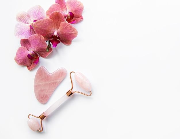 Rodillos de jade de masaje facial y flores de orquídeas sobre fondo blanco.