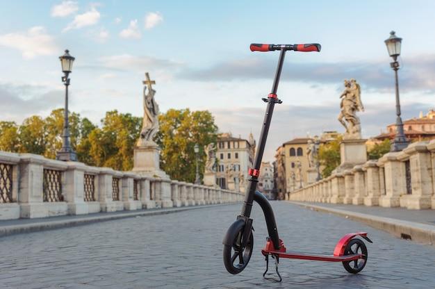 Rojo empuje scooters contra el telón de fondo del ponte sant angelo en roma, italia.