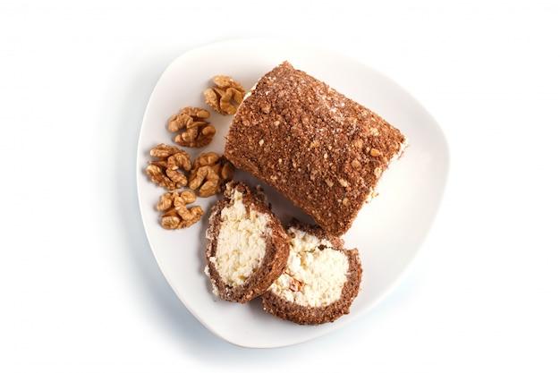 Roll cake con cuajada y nueces aisladas en blanco