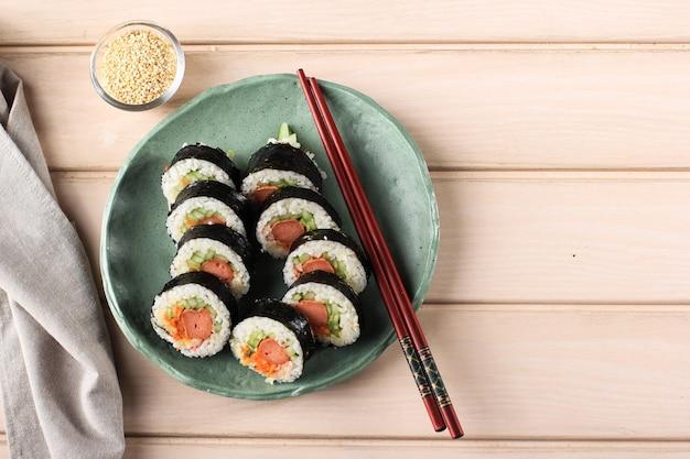 Roll gimbap coreano (kimbob o kimbap) hecho de arroz blanco al vapor (bap) y varios otros ingredientes, como kyuri, zanahoria, salchicha, palito de cangrejo o kimchi y envuelto con algas marinas