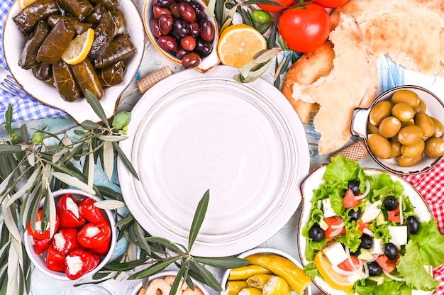 Rollitos de col turca y diversos aperitivos de la cocina nacional. arroz en hojas de uva y aceitunas. comida para un almuerzo tradicional oriental. espacio libre para texto, plato vacío