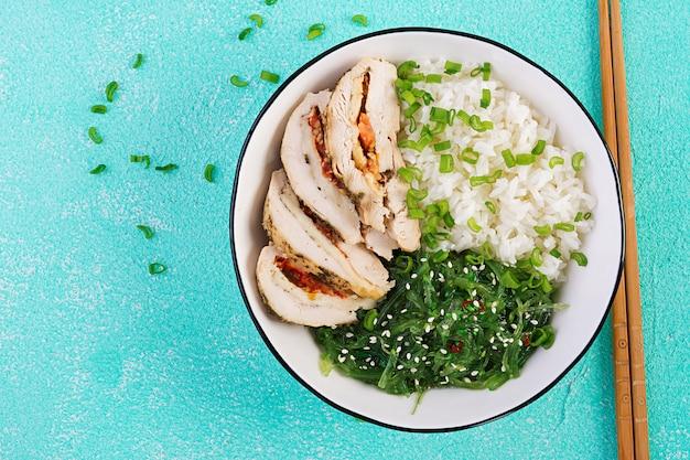 Rollitos de pollo, arroz, chuka y cebolla verde en un tazón blanco con palillos