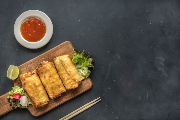 Rollitos de primavera de vegetales fritos con ingredientes frescos servidos y salsa agria en un restaurante oriental