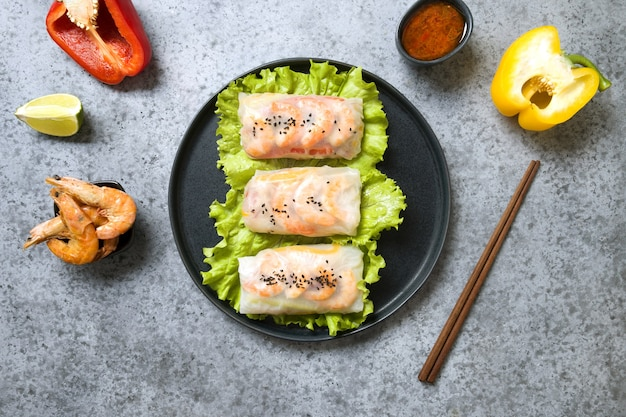 Rollitos de primavera vietnamitas con langostinos e ingredientes en papel de arroz sobre fondo gris. vista desde arriba. cocina asiática. orientación horizontal.