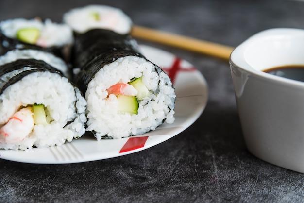 Rollitos de sushi, salsa de soja y palillos.