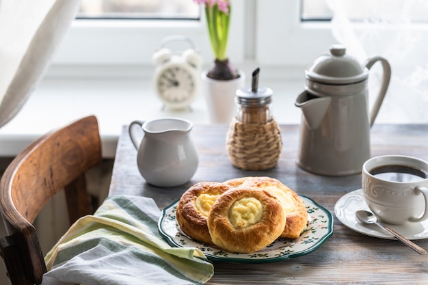 Rollitos de tarta de queso para el desayuno en una mesa de madera junto a la ventana con un gato