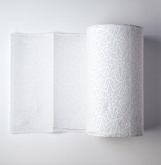 Rollo blanco expandido de papel de cocina sobre un fondo blanco.