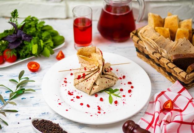 Rollo de bocadillo de lavash con queso y semillas granadas, pan, verduras y sorbete en un plato blanco. bocadillo