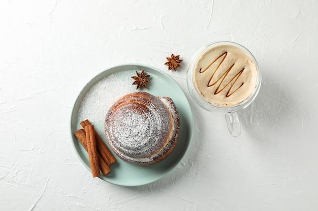 Rollo de canela sabroso con ingredientes, capuchino en mesa de cemento blanco.