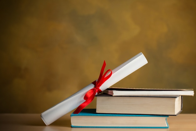 Rollo de certificado, libros, bolígrafo sobre mesa de madera con copyspace