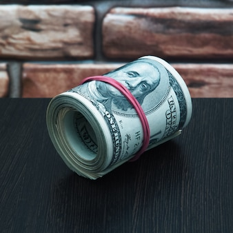 Un rollo de cien billetes estadounidenses en efectivo de cerca contra una pared de ladrillos.
