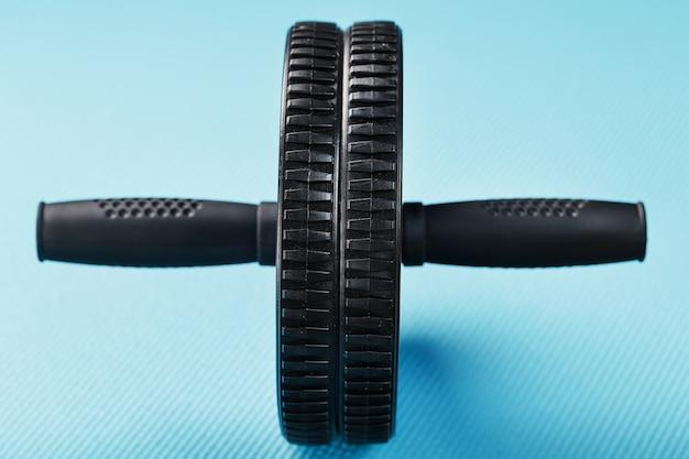 Rollo deportivo para entrenar músculos y abdominales sobre la alfombra azul.