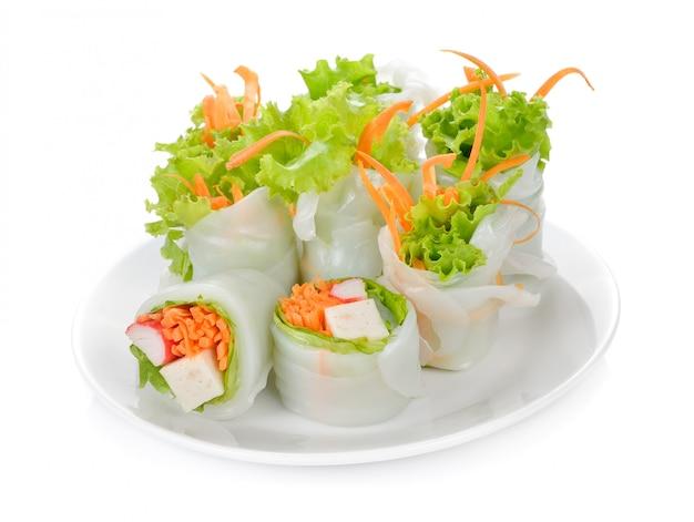 Rollo de la ensalada de las verduras frescas en tubo de los tallarines en el plato aislado en blanco