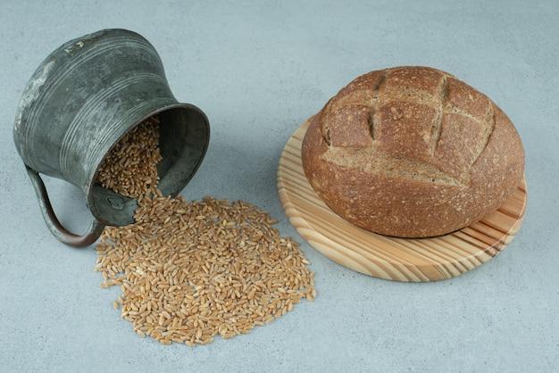 Rollo de pan de centeno sobre tabla de madera con taza de cebada