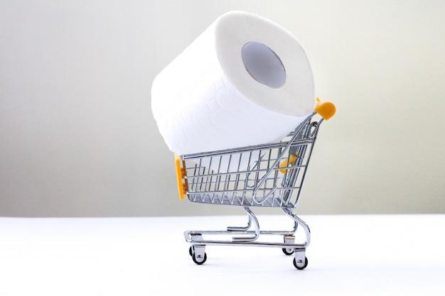 Rollo de papel higiénico blanco con un carrito de compras sobre un fondo blanco.