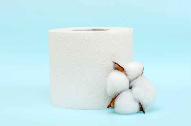 Rollo de papel higiénico blanco y flor de algodón sobre fondo azul.