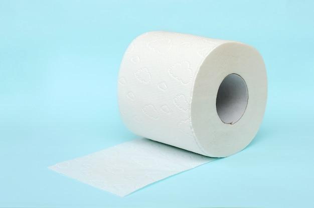 Rollo de papel higiénico blanco sobre fondo azul.