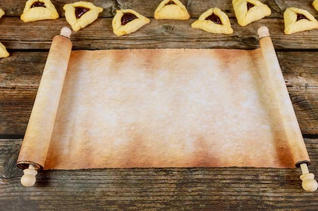 Rollo de papiro con galletas purim en madera