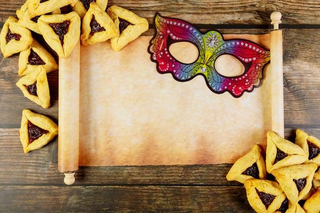 Rollo de papiro con galletas purim y máscara.