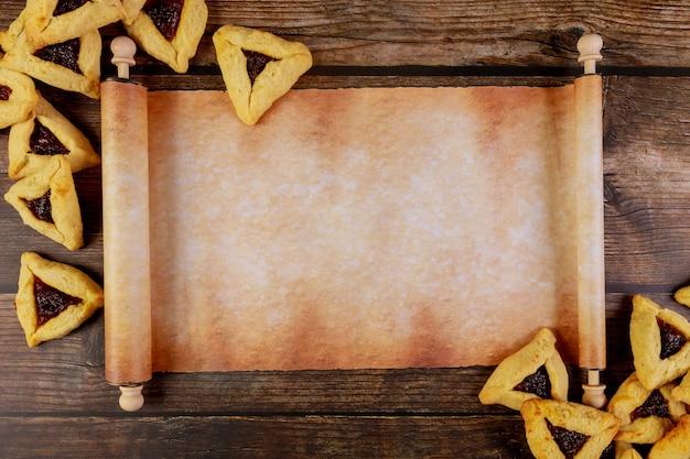 Rollo de papiro con galletas de purim sobre fondo de madera.