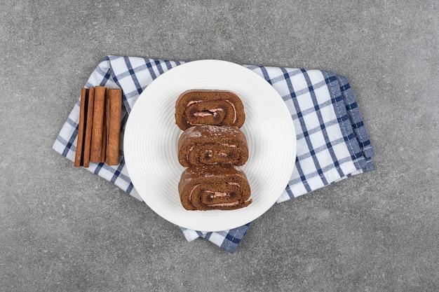 Rollo de pastel de chocolate en un plato blanco con canela