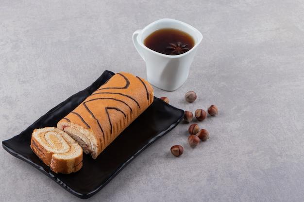 Rollo de pastel fresco con taza de té en placa negra sobre fondo gris.