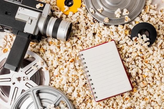 Rollo de película y cámara de videocámara con bloc de notas en espiral sobre palomitas de maíz.