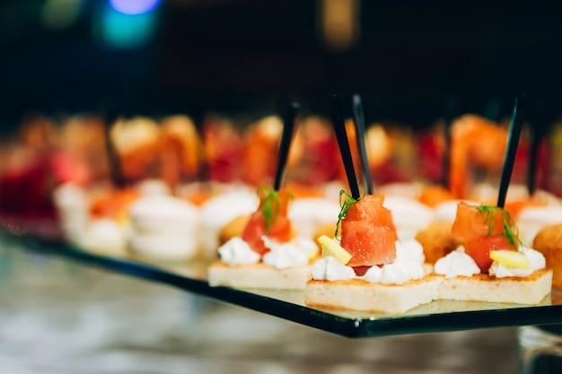 Rollo de pescado rojo en un pincho. filete de salmón con eneldo y limón. plato con pequeños bocadillos