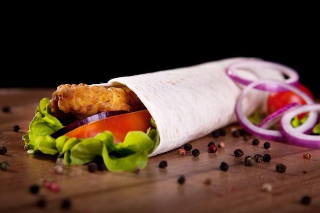 Rollo de pollo con lechuga tomate cebolla y pimiento sobre una mesa de madera y fondo negro.