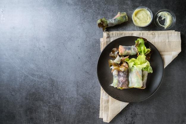 Rollo de primavera de vegetales frescos, alimentos limpios, ensalada para perder peso, sobre fondo oscuro