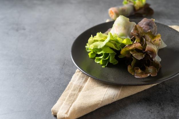 Rollo de primavera de vegetales frescos, comida limpia, ensalada para perder peso, sobre fondo oscuro