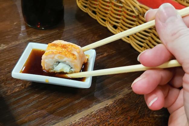 Rollo de sushi al horno, mano con palillos de bambú con un plato sobre salsa de soja en un tazón de cerámica