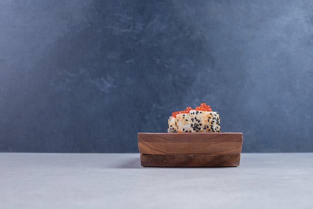 Rollo de sushi de alaska con plato de madera con caviar rojo.