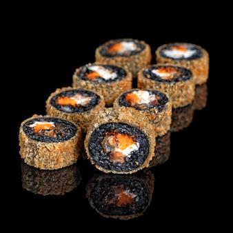 Rollo de sushi caliente japonés en tempura aislado sobre fondo negro. rollo asiático con arroz negro, salmón, aguacate, pepino, queso philadelphia