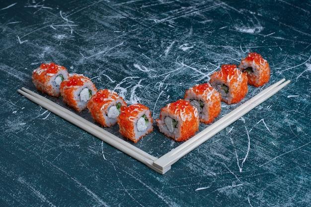 Rollo de sushi california decorado con caviar rojo sobre azul con palillos.