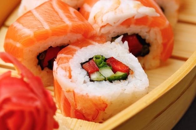 Rollo de sushi cubierto con salmón y gambas cerrar