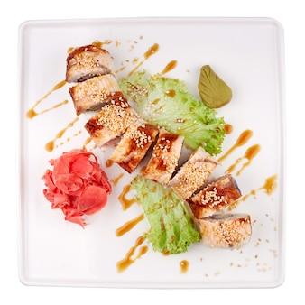 Rollo de sushi de dragón dorado. rollos de sushi con caviar de pez volador, atún, anguila, pepino, semillas de sésamo y queso crema dentro y en pizarra negra aislada.