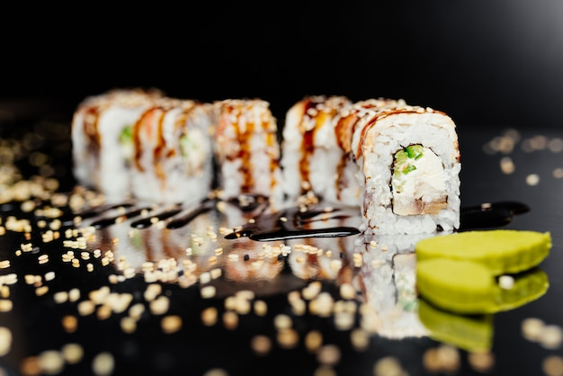 Rollo de sushi dragón de oro hecho de nori, arroz marinado, queso, pepino, unangile