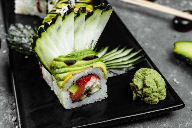 Rollo de sushi dragón verde con anguila, aguacate, pepino y jengibre, acompañado de camarón tempura frito