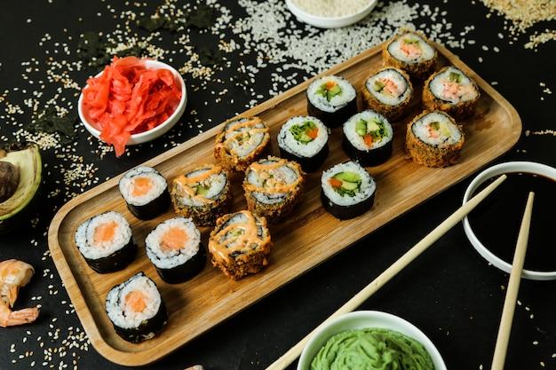 Rollo de sushi en el escritorio con vista superior de salsa