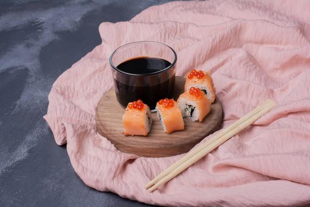 Rollo de sushi de filadelfia, salsa de soja y palillos sobre un mantel rosa.