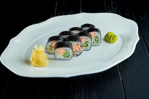 Rollo de sushi futomak con salmón, pepino en un plato blanco sobre un fondo de madera negra con jengibre y wasabi.