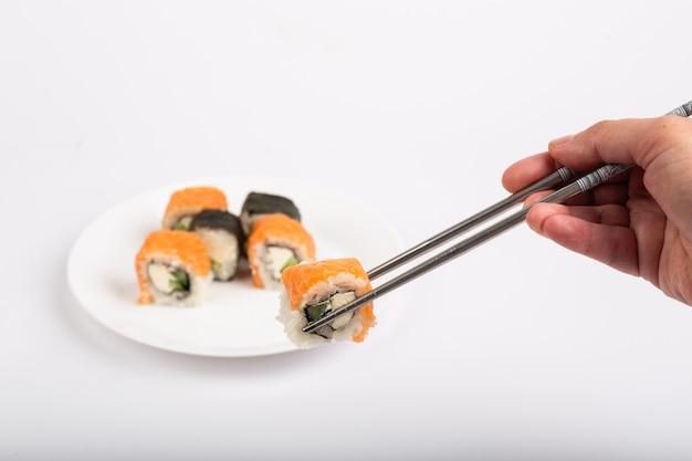 Rollo de sushi en un plato, rollo de sushi en una tableta, fondo blanco, rollo de sushi y mano con palillos