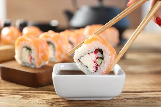 Rollo de sushi sabroso con palillos de madera y salsa en un tazón