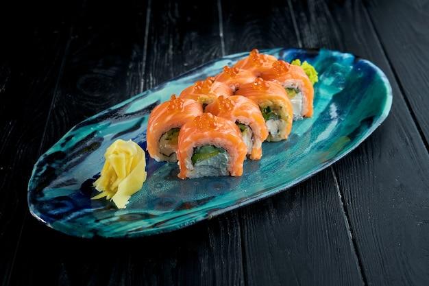 Rollo de sushi con salmón, aguacate y queso crema en una placa azul. rollo de filadelfia