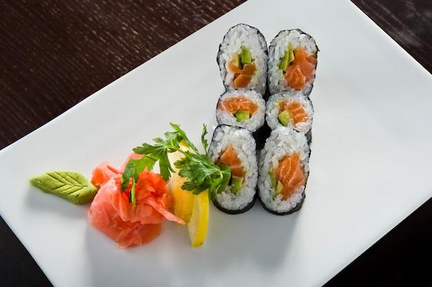 Rollo de sushi con salmón y camarones tempura.